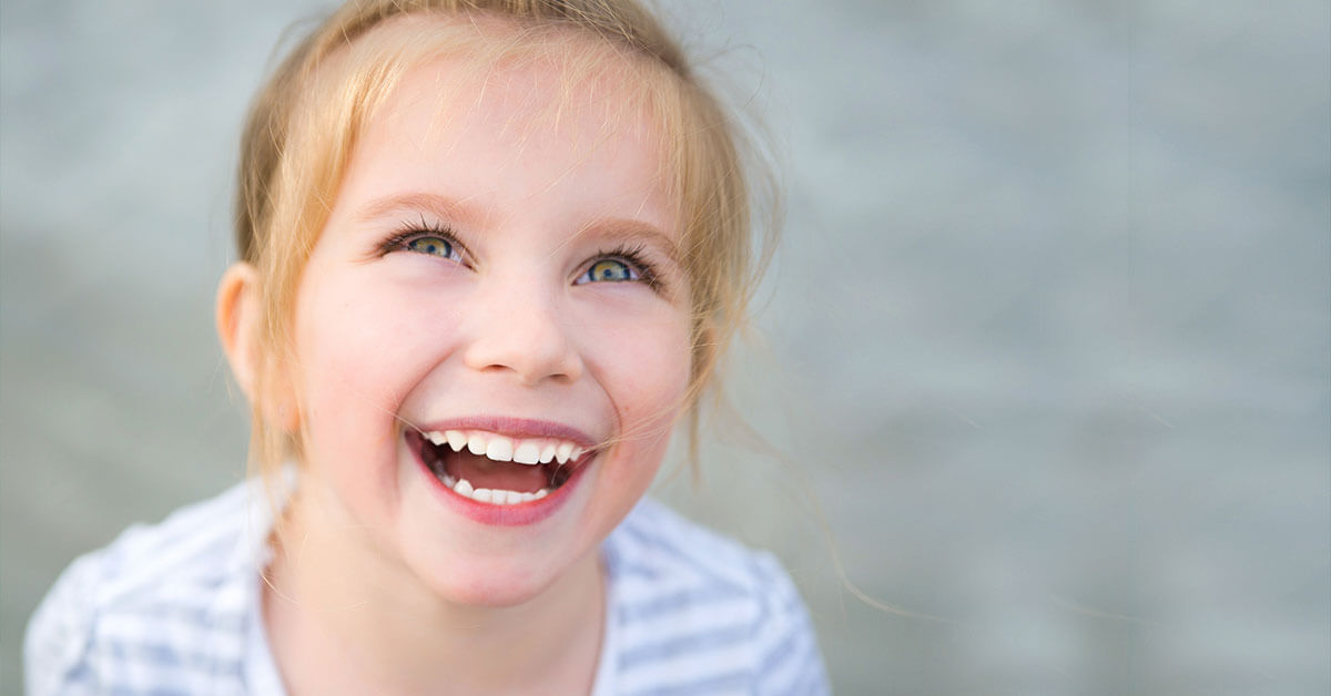 Little girl smiling showing white teeth
