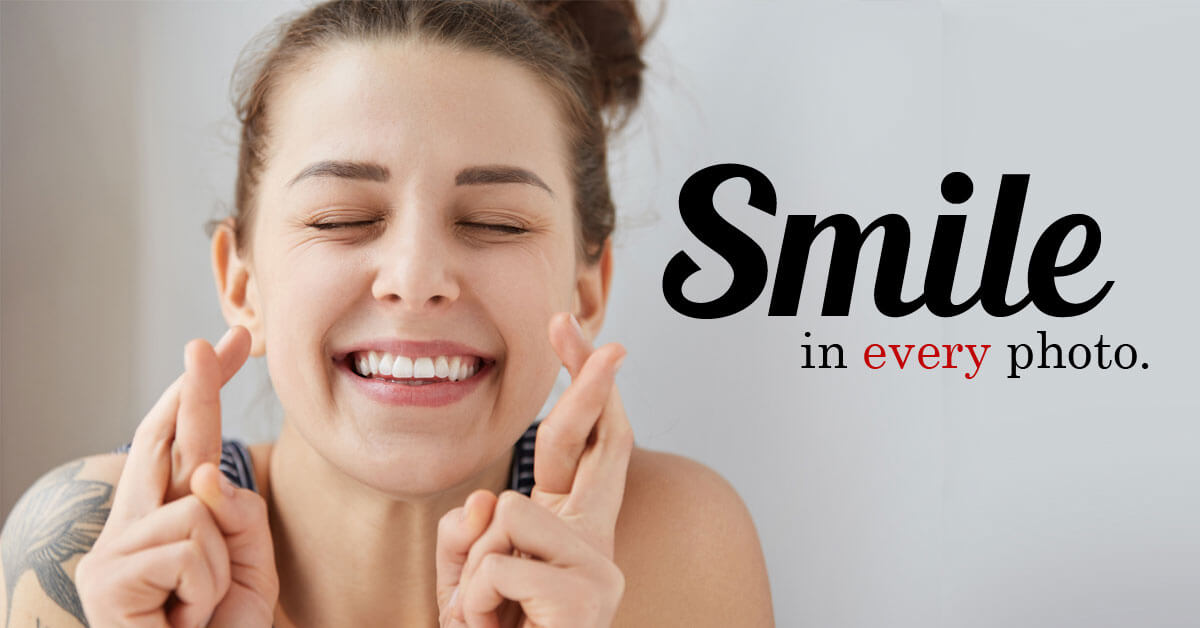 Young beautiful woman smiling with fingers crossed